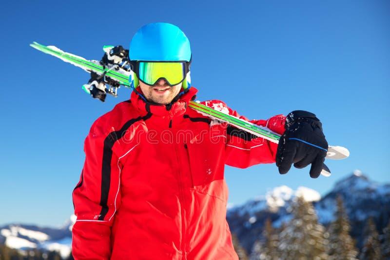 Esquiador caucasiano atrativo novo com o esqui nos cumes suíços prontos para esquiar foto de stock royalty free