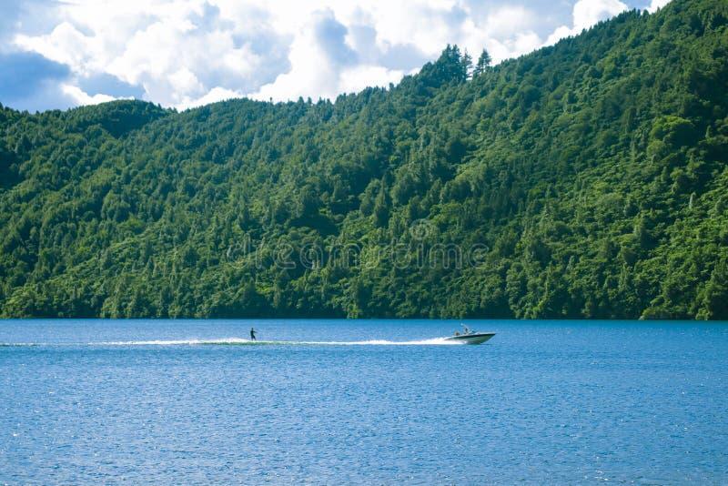 Esquiador da água no lago com barco Embarque da vigília da pessoa no dia ensolarado foto de stock royalty free