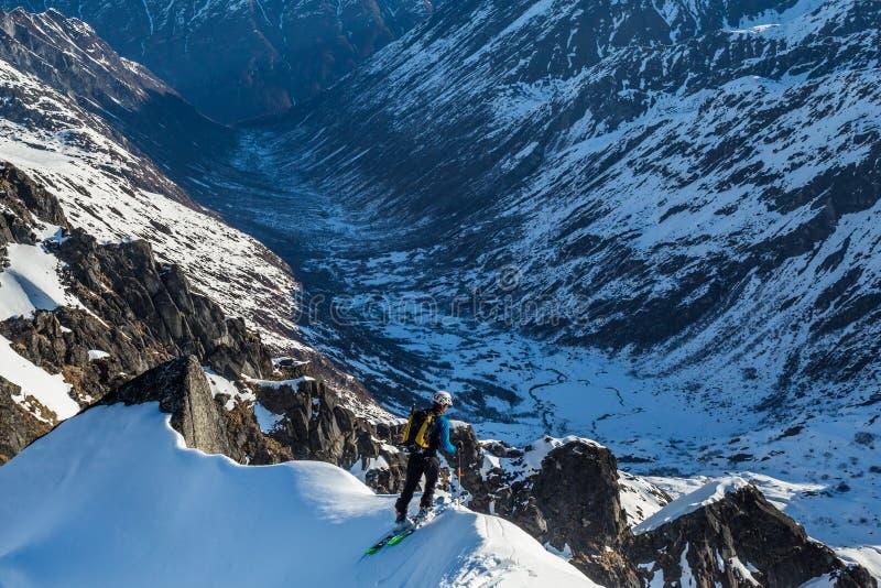 Esquiador de Backcountry que espreita sobre a borda íngreme de um cume da cimeira na drenagem da angra de Bartholf foto de stock royalty free