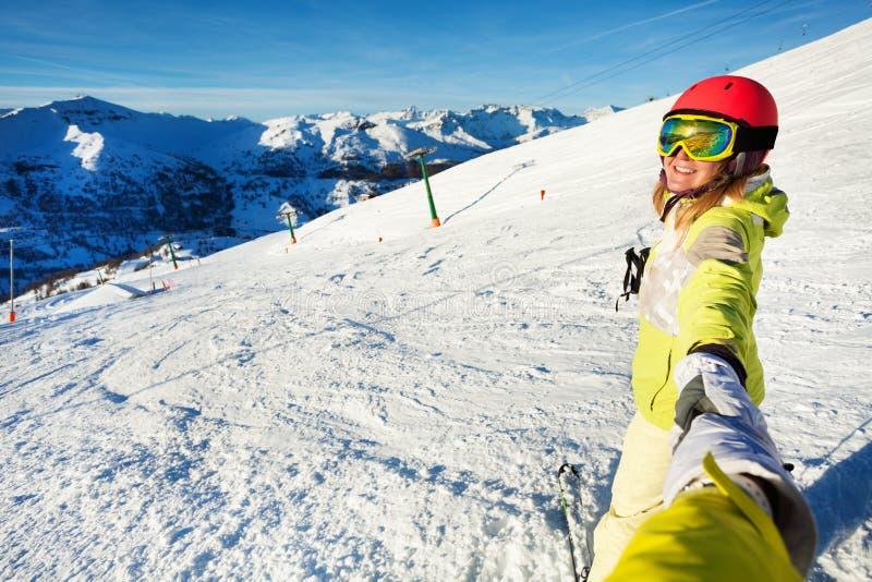 Esquiador de sexo femenino sonriente que toma el selfie contra cuesta imagen de archivo