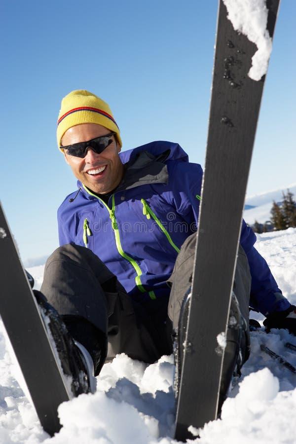Esquiador de sexo masculino que se sienta en nieve después de caer imagen de archivo libre de regalías