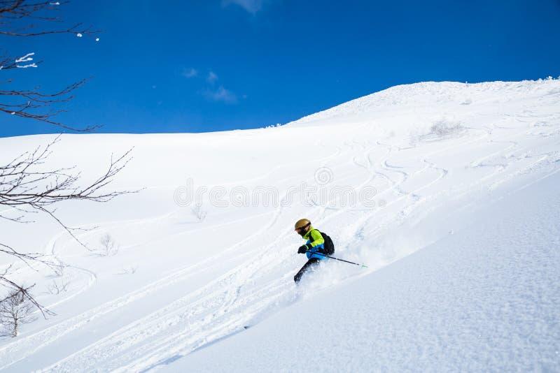 Esquiador de Telemark en cuesta backcountry del polvo de la montaña de Niseko imágenes de archivo libres de regalías
