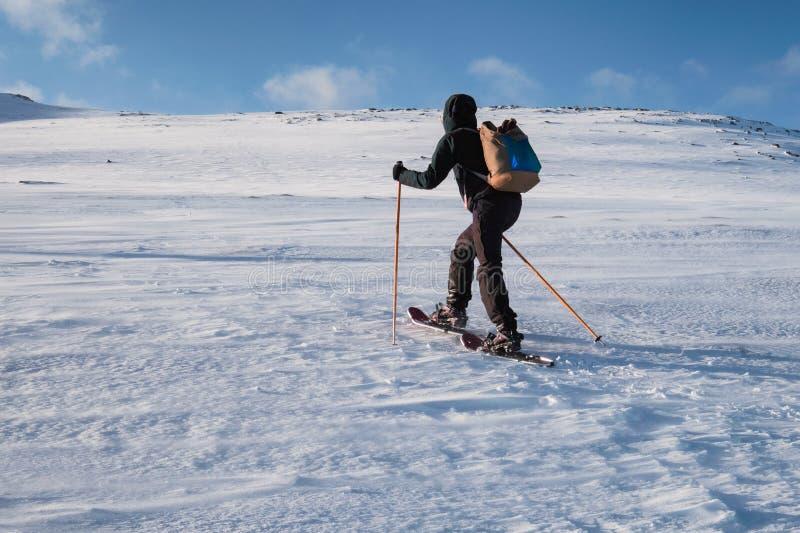 Esquiador del hombre con emigrar los polos que suben en la colina nevosa foto de archivo