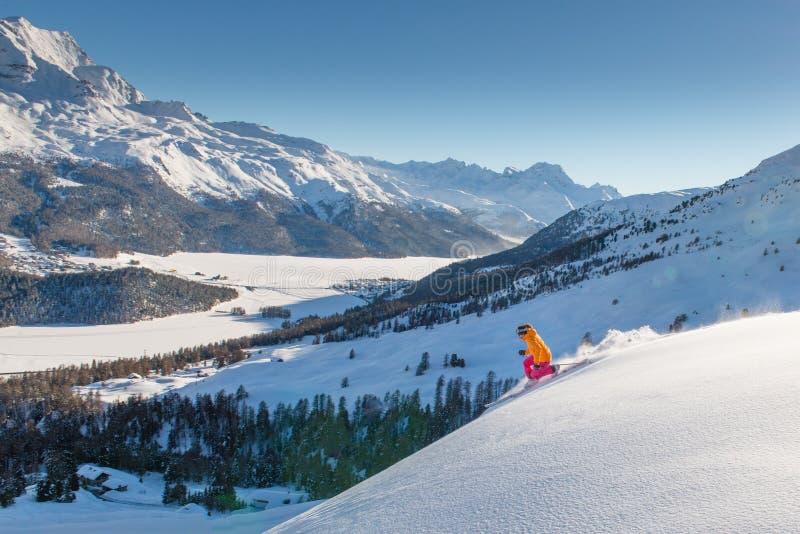 Esquiador del telemark de la muchacha en la cuesta sobre el valle de los lagos foto de archivo
