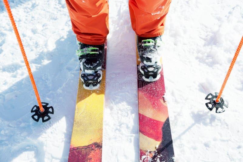 Esquiador do atleta dos pés em uma laranja total em um esqui do esporte na neve em um dia ensolarado O conceito de esportes de in imagens de stock