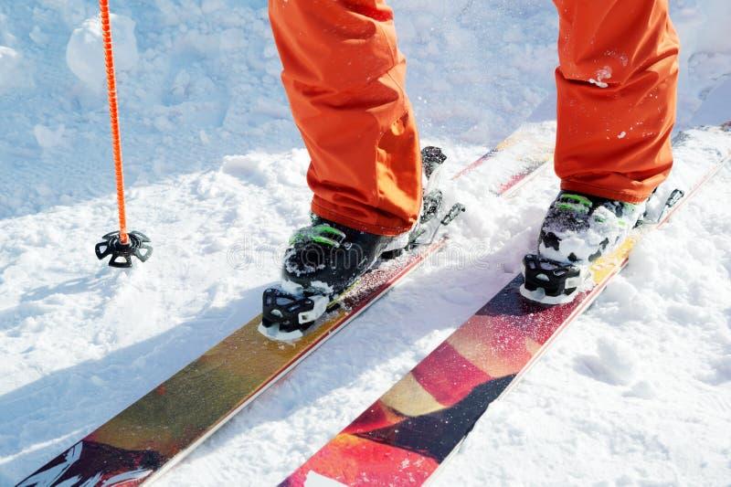 Esquiador do atleta dos pés em uma laranja total em um esqui do esporte na neve em um dia ensolarado O conceito de esportes de in foto de stock