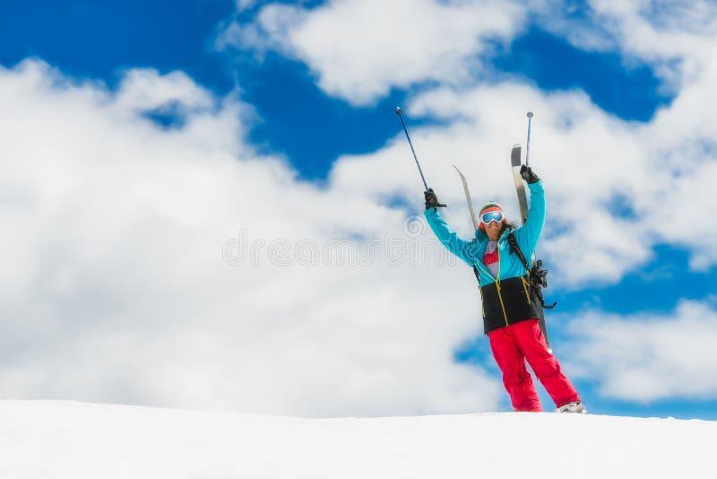 Esquiador do freeride da menina, aumentos suas mãos antes da descida do th fotografia de stock