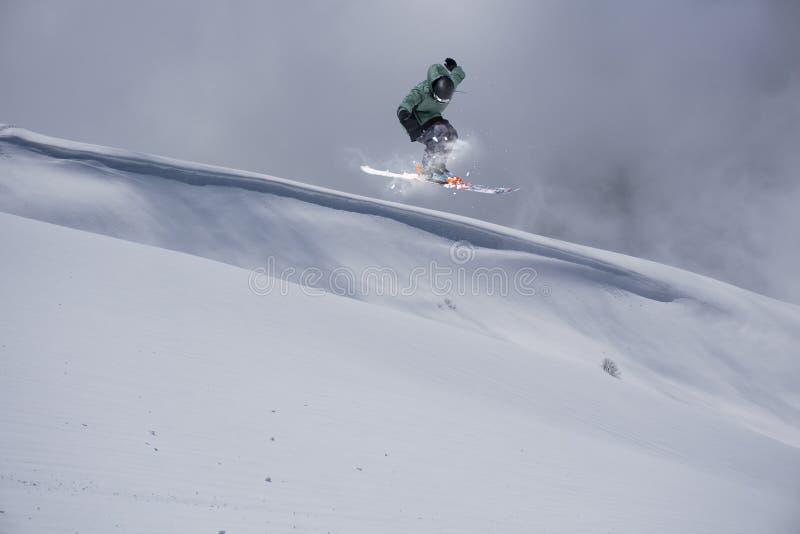 Esquiador do vôo em montanhas Esporte de inverno extremo foto de stock royalty free