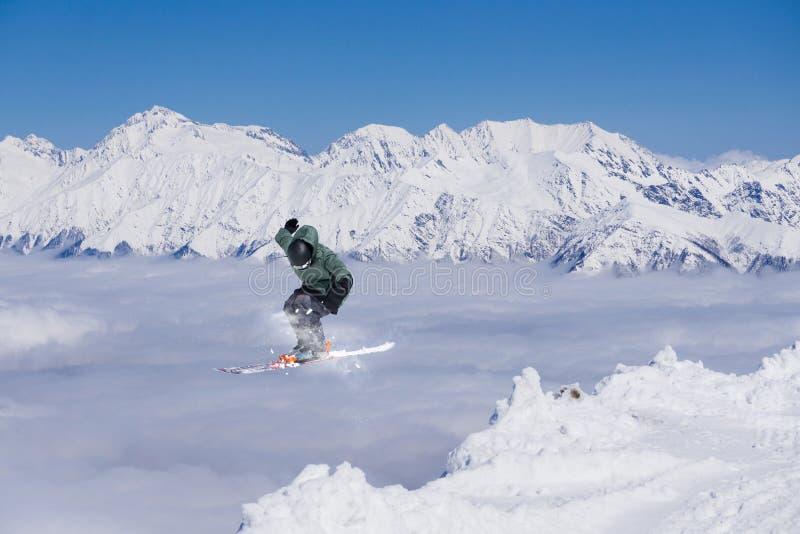 Esquiador do voo em montanhas nevado Esporte de inverno extremo, esqui alpino foto de stock royalty free