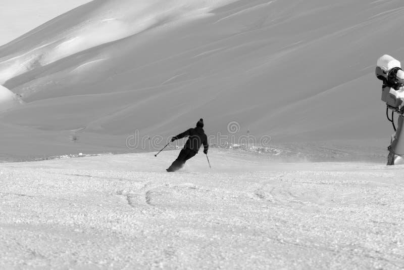 Esquiador em declive na inclinação nevado preparada do esqui com o canhão da neve no dia de inverno do sol fotografia de stock