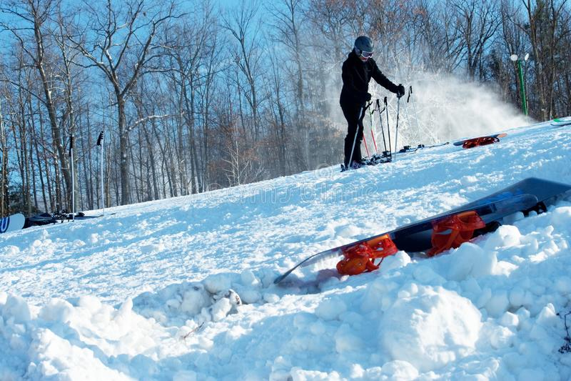 Esquiador em declive que guarda Polos ao liberar botas imagens de stock