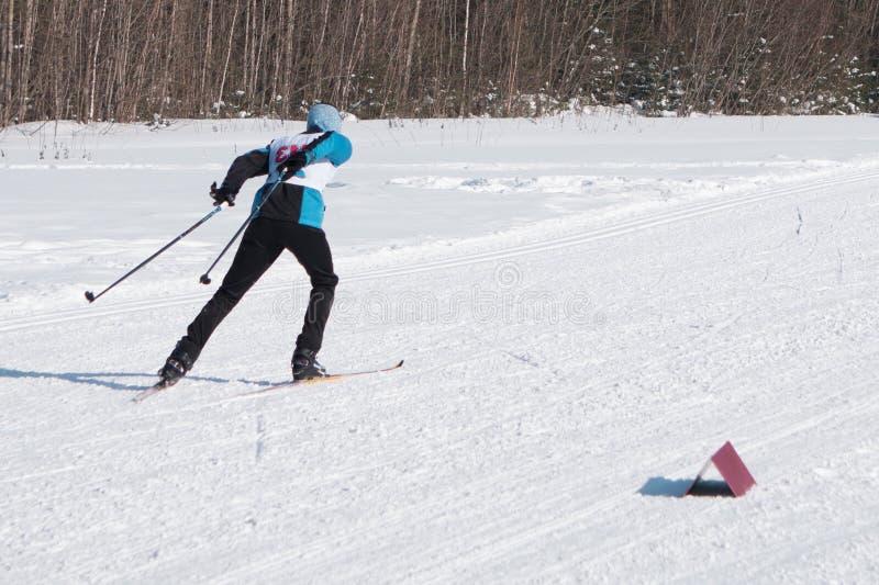 Esquiador en montañas, piste preparado y día asoleado imagen de archivo