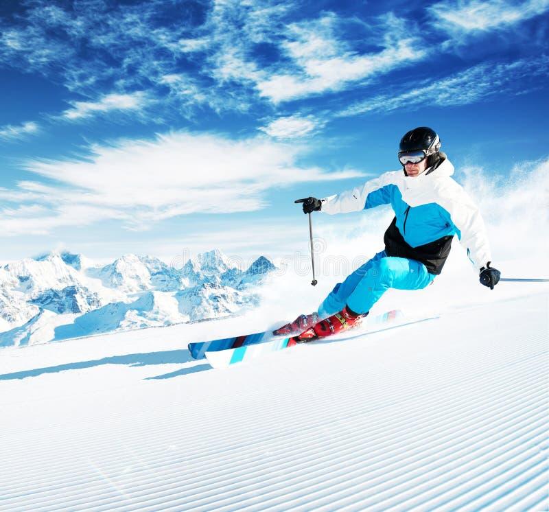 Esquiador en montañas, piste preparado y día asoleado fotos de archivo libres de regalías