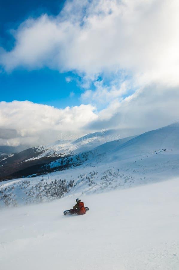Esquiador en montañas, piste preparado y día asoleado imagenes de archivo