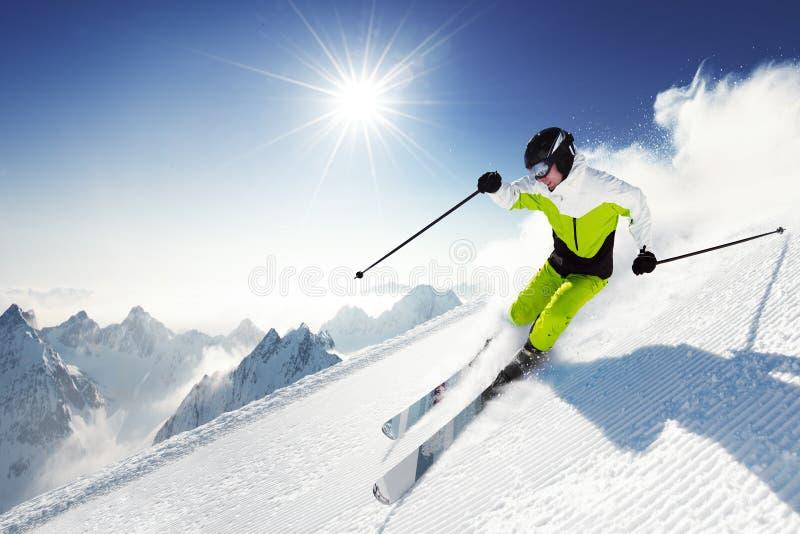 Esquiador en montañas, piste preparado y día asoleado imagen de archivo libre de regalías