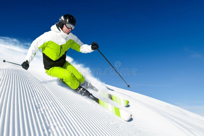 Esquiador en montañas, piste preparado y día asoleado fotos de archivo