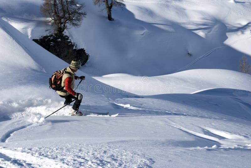 Esquiador en una cuesta en nieve del polvo fotografía de archivo libre de regalías
