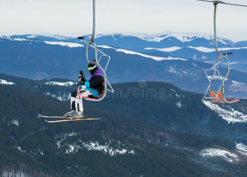 Esquiador en una plataforma en un fondo de las altas montañas de la nieve imagen de archivo
