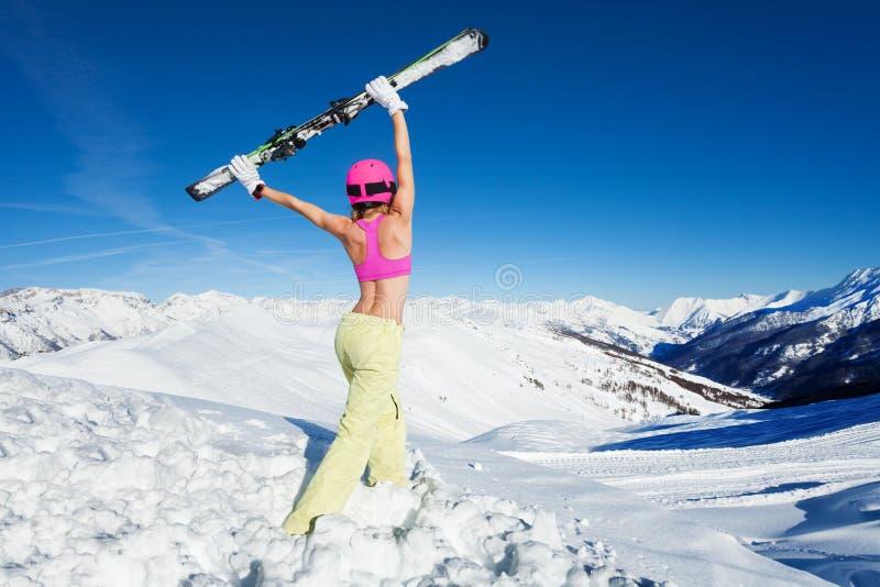 Esquiador fêmea no sutiã dos esportes que levanta acima dos pares de esqui imagem de stock
