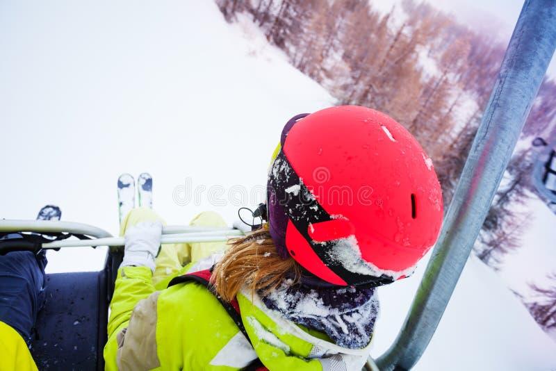 Esquiador fêmea que senta-se na telecadeira na montanha alta foto de stock royalty free