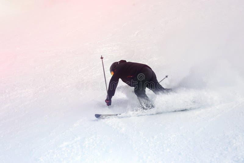 Esquiador maduro caido durante en declive en la estación de esquí en invierno Accidente en la cuesta del esquí debida desatar el  foto de archivo