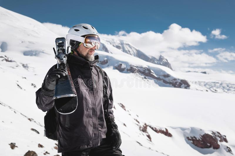 Esquiador masculino farpado do retrato envelhecido contra o fundo de montanhas de C?ucaso neve-tampadas Um esqui vestindo do home fotografia de stock royalty free