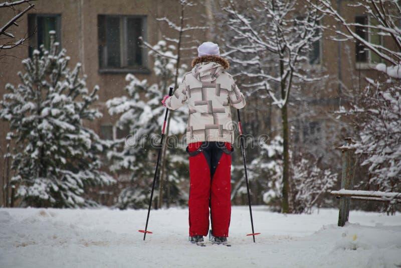 Esquiador na cidade no fundo de uma casa esporte de inverno - esqui corta-mato fuga da neve para esquiar vida perto da floresta imagem de stock