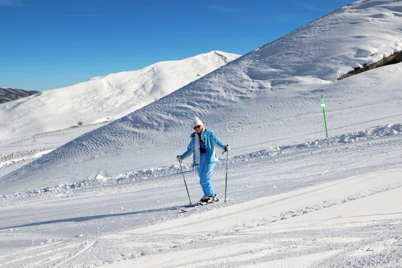 Esquiador na inclinação nevado do esqui da luz solar no dia agradável do sol fotos de stock royalty free
