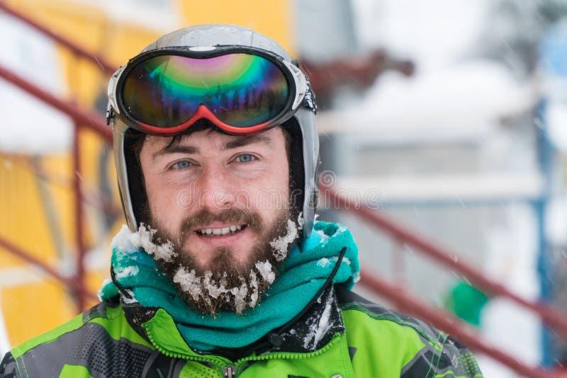 Esquiador na máscara na cara de um homem da neve e de esquis da neve imagem de stock royalty free