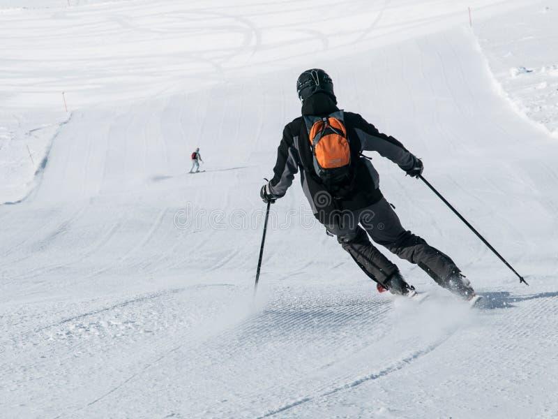 Esquiador no esqui em declive preto em uma inclinação do esqui Vista da parte traseira imagem de stock royalty free