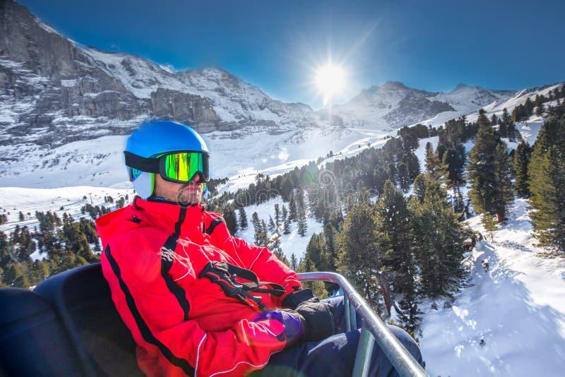 Esquiador novo no elevador de esqui na estância de esqui famosa em cumes suíços, região de Jungfrau, Suíça fotos de stock royalty free