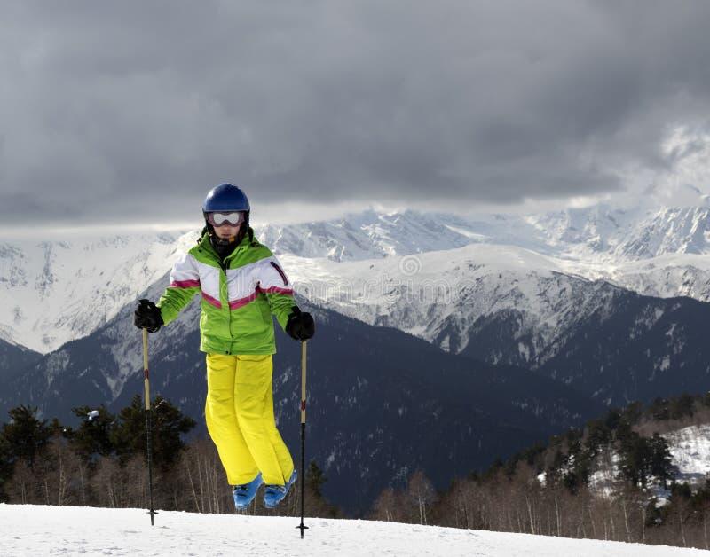Esquiador novo que salta com os polos de esqui em montanhas do sol e em g nebuloso fotos de stock