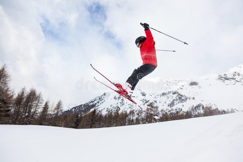 Esquiador pequeno que salta na neve. imagem de stock
