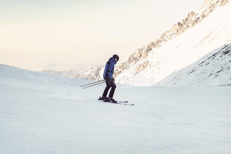 Esquiador que esquía cuesta abajo en altas montañas El atleta es un aficionado, no un profesional, prudente con el miedo rueda ab foto de archivo libre de regalías