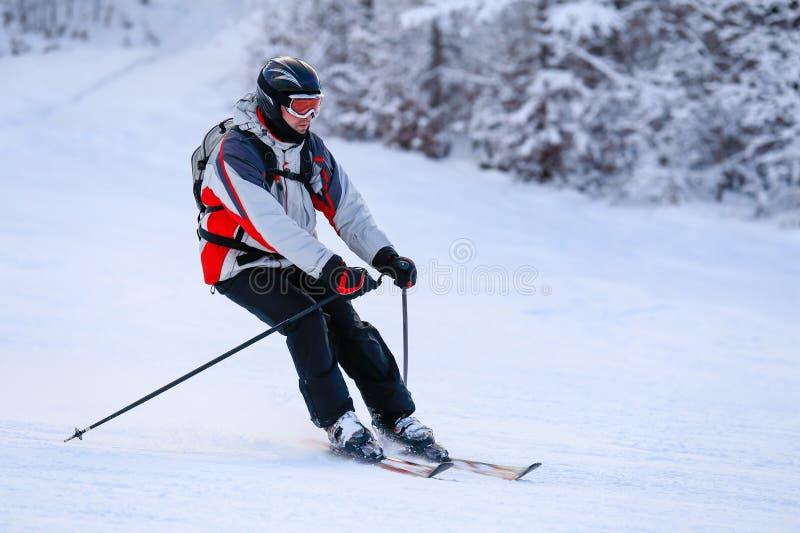 Esquiador que esquía cuesta abajo en montañas del invierno imagen de archivo libre de regalías