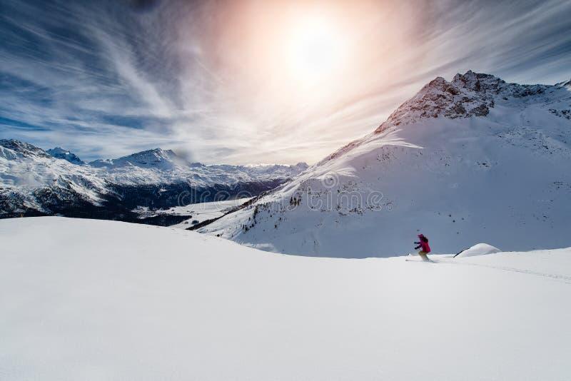 Esquiador que esquia para baixo nas montanhas altas contra o por do sol imagem de stock royalty free