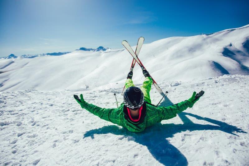 Esquiador que miente en una cuesta del esquí en un día soleado fotos de archivo