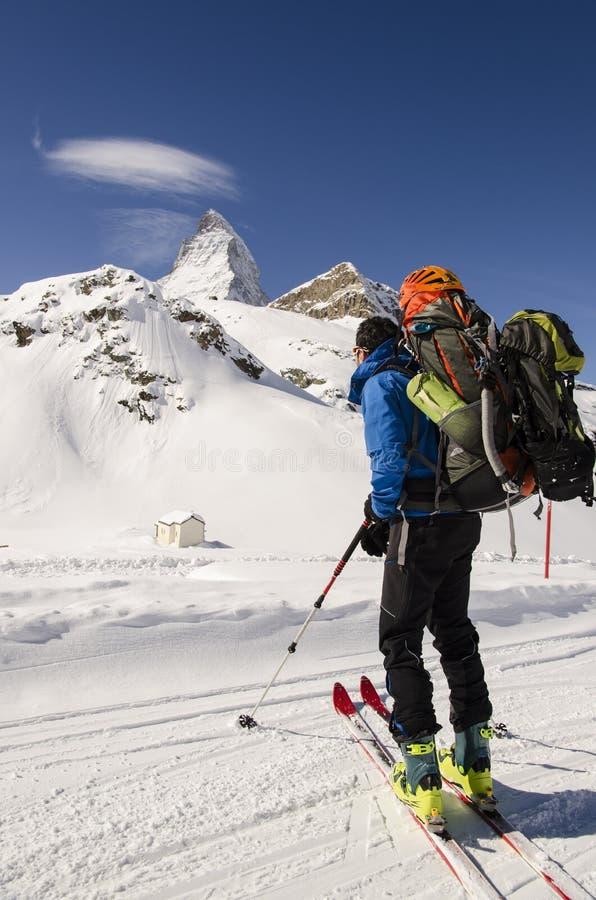 Esquiador que mira las montañas nevadas imagen de archivo