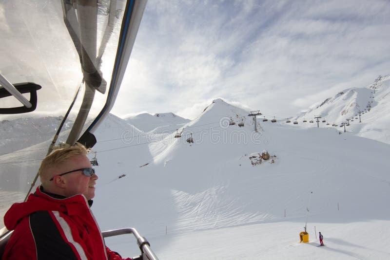 Esquiador que se sienta en la elevación de silla fotografía de archivo