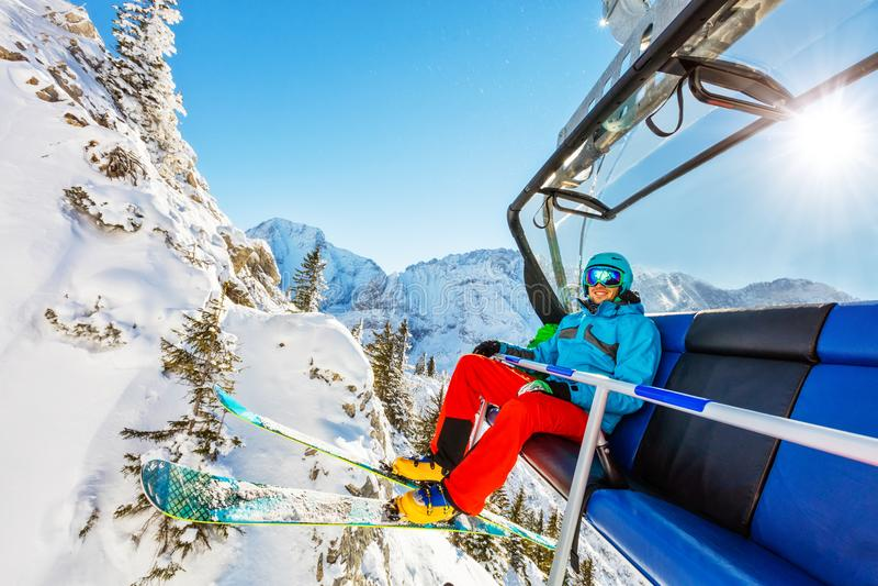 Esquiador que senta-se no elevador de esqui nas montanhas altas durante o dia ensolarado imagem de stock royalty free