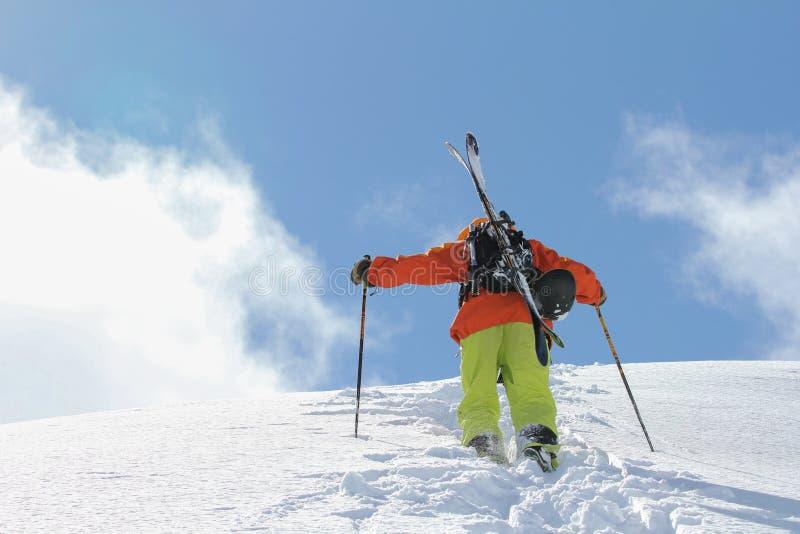 Esquiador que sube una montaña nevosa fotografía de archivo libre de regalías