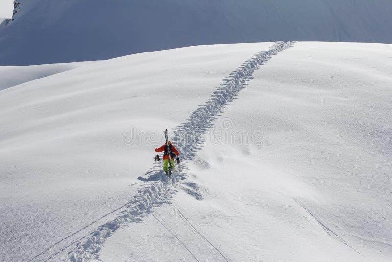 Esquiador que sube una montaña nevosa imagen de archivo