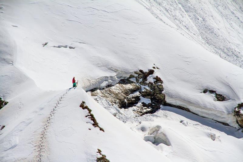 Esquiador que sube una montaña nevosa fotos de archivo