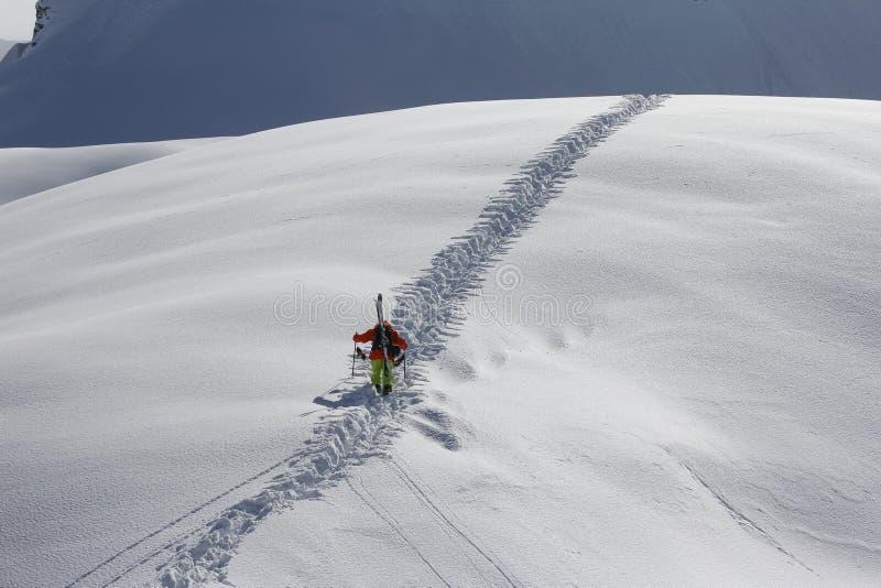Esquiador que sube una montaña nevosa imagenes de archivo