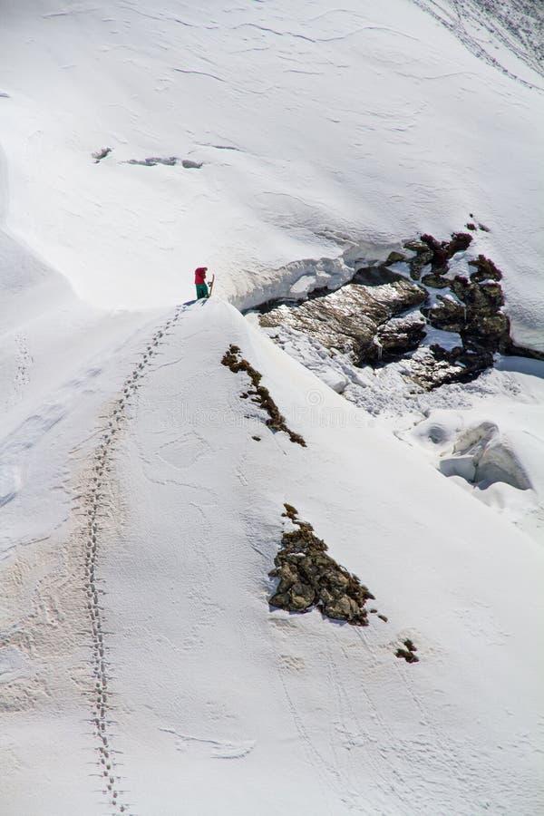 Esquiador que sube una montaña nevosa imagen de archivo libre de regalías