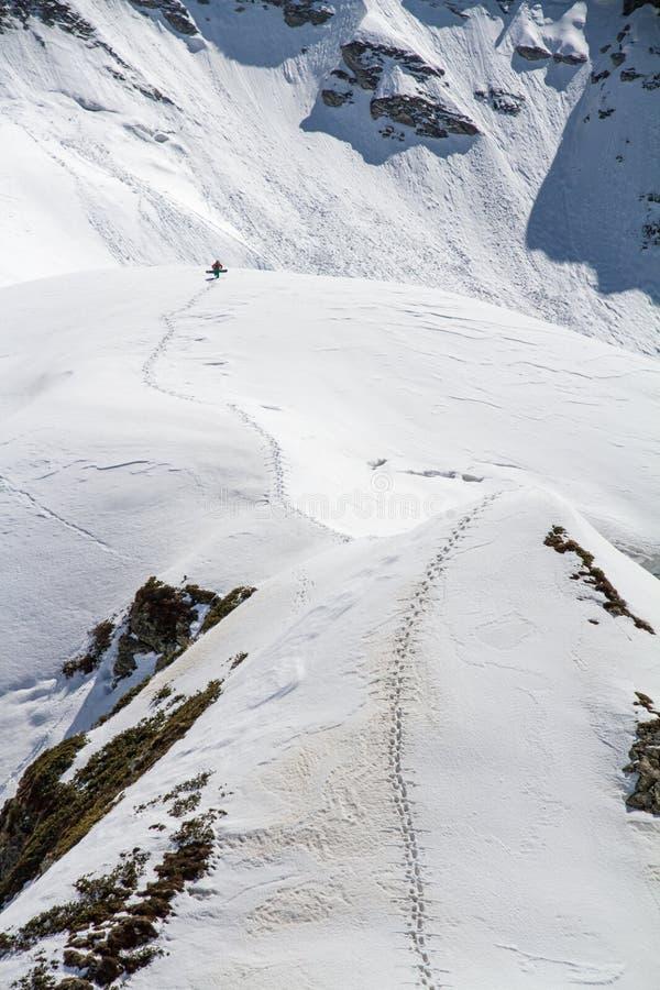 Esquiador que sube una montaña nevosa fotografía de archivo