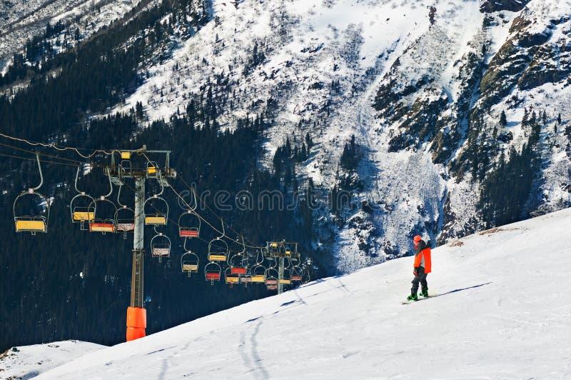 Esquiador que vai abaixo da inclinação sob o elevador de esqui Teleférico nas montanhas fotografia de stock royalty free