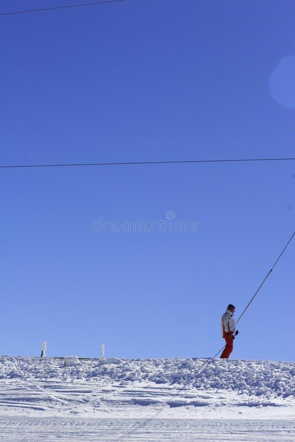 Esquiador solitário em um elevador do arrasto imagens de stock