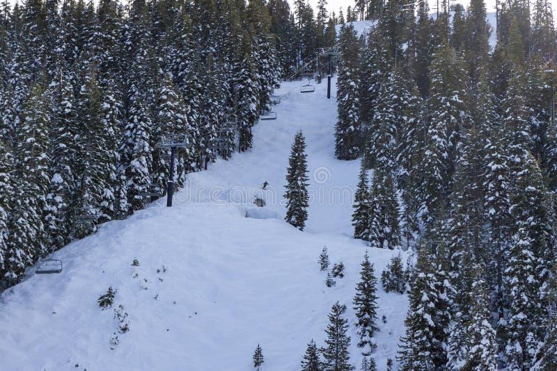 Esquiador solitario en un funcionamiento en declive a la una de las muchas bazofias en Squaw Valley imagen de archivo