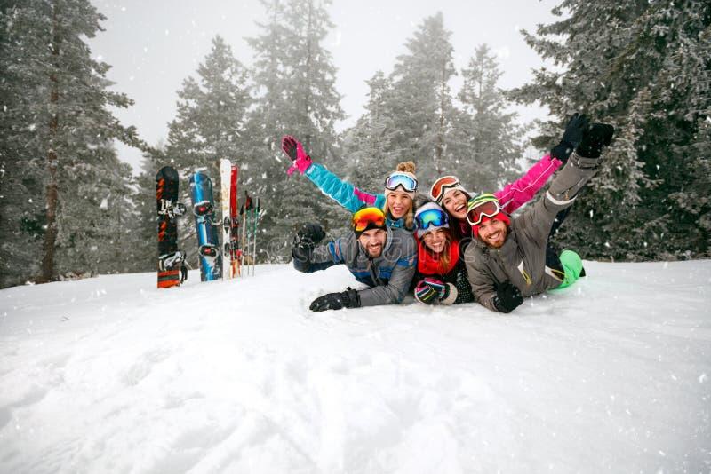 Esquiadores alegres que encontram-se na neve e que têm o divertimento imagem de stock royalty free